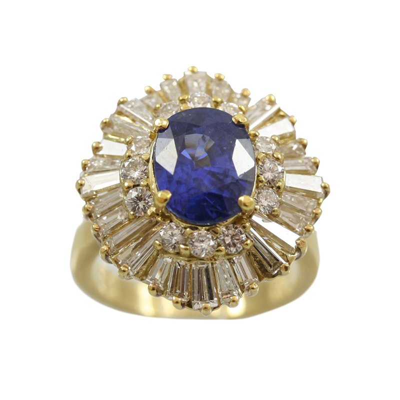 This 18 Karat Yellow Gold Sapphire And Diamond Ring Is Gorgeous! The Ring Contains One Oval Cut Sapphire Prong Set In Its Center Which Is Surrounded By Twelve Full Cut Diamond Prong Set And With Twenty Eight Tapered Baguette Diamonds Delicately Set Baller